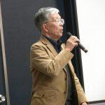 司会進行と参加者の歌声をリードするキワカーイ氏 (1)
