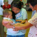 恐る恐る赤ちゃんを抱っこする小中生