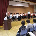 指揮者梅津信一さん率いるラ・ジュネスのメンバーと司会の大内公江さん